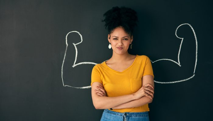 Shot of a woman posing with a chalk illustration of flexing muscles against a dark background